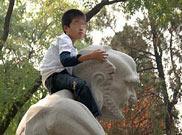 一名小游客爬上雕像拍照留念
